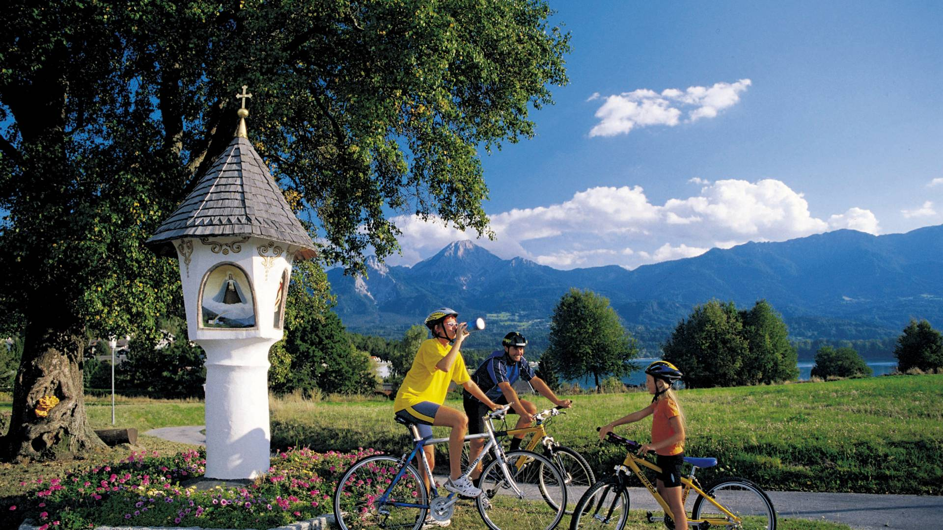 Familie beim Radfahren vor einem Bildstock