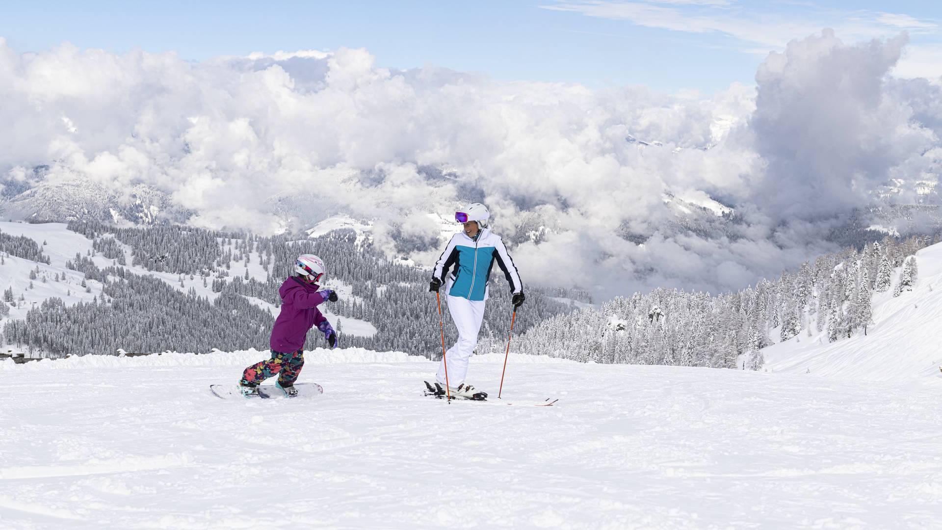 """<p>Ein Kind auf einem Snowboard fährt auf eine Frau auf Skiern zu. Die Skipiste ist perfekt präpariert und die Landschaft rundherum tief verschneit. Der Himmel ist blau nur über dem Tal sind ein paar Wolken zu sehen. Dieses Bild entstand im Skigebiet Nassfeld in Kärnten, dem Skigebiet an der Grenze zu Italien, welches auch zu den """"TOP 10 Skigebieten"""" Österreichs gehört.</p>"""