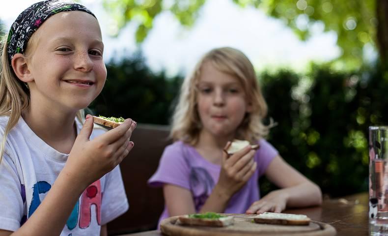 Mädchen genießen das frische Brot im Lesachtal