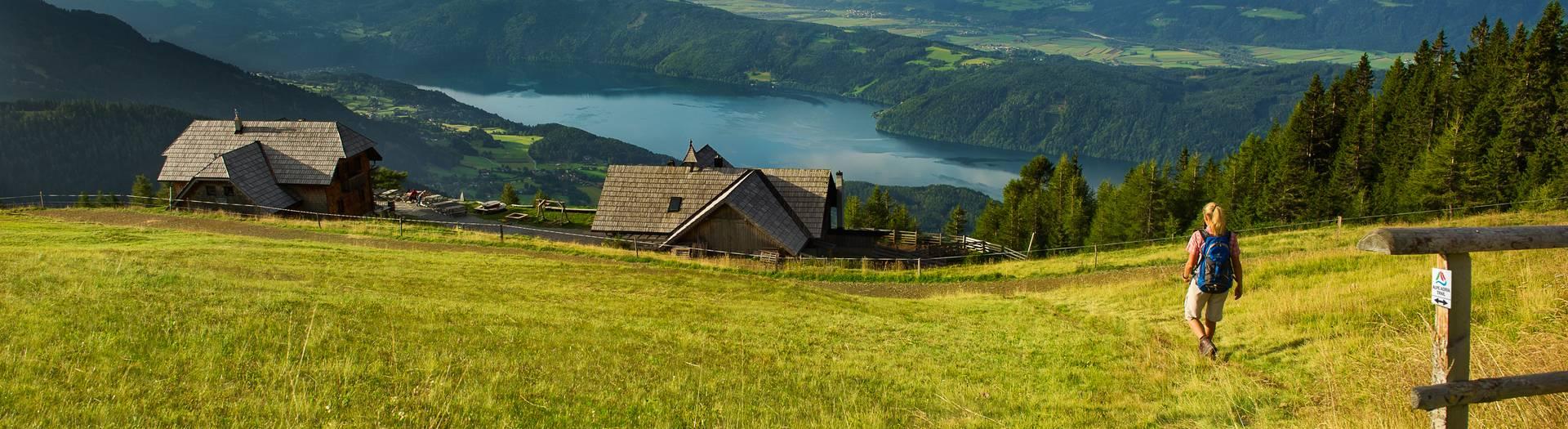 Wanderer auf dem Alpe Adria Trail mit Blick auf See