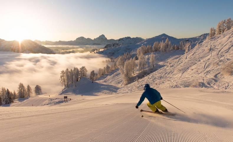 Mit den Skiern die Piste herunterfahren.